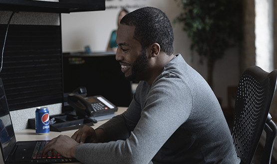 man on a laptop at his desk working and smiling