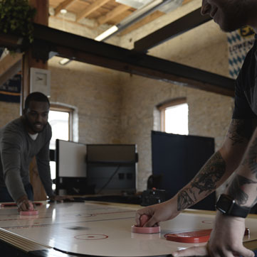 Two Trivera employees playing air hockey