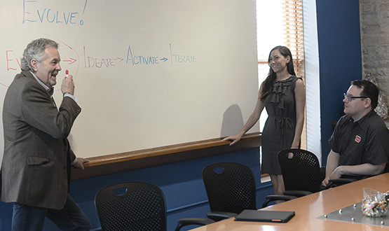 man and woman at white board in a conference room